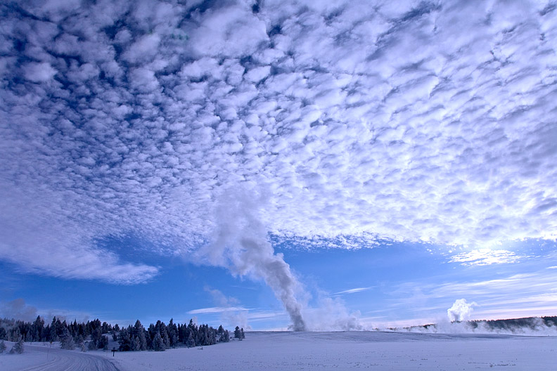 An erupting geyser produces plumes of steam that form a pattern.