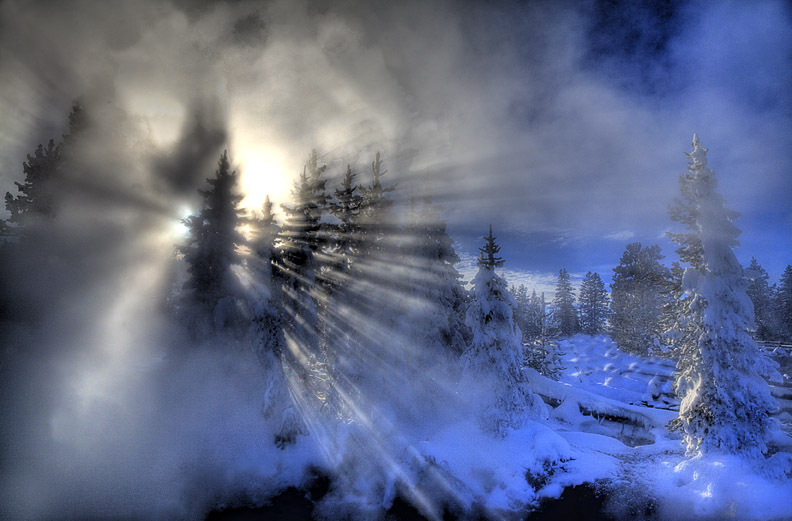 The winter sun fights to get shine through steam and fog at a frigid Yellowstone.