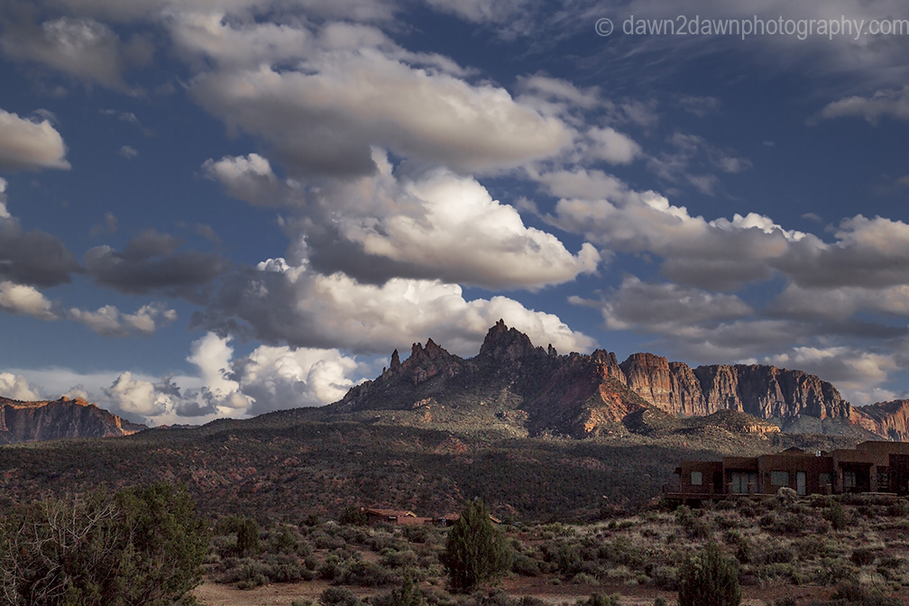 White puffy clouds surround Eagle Crags near Zion National Park, Utah