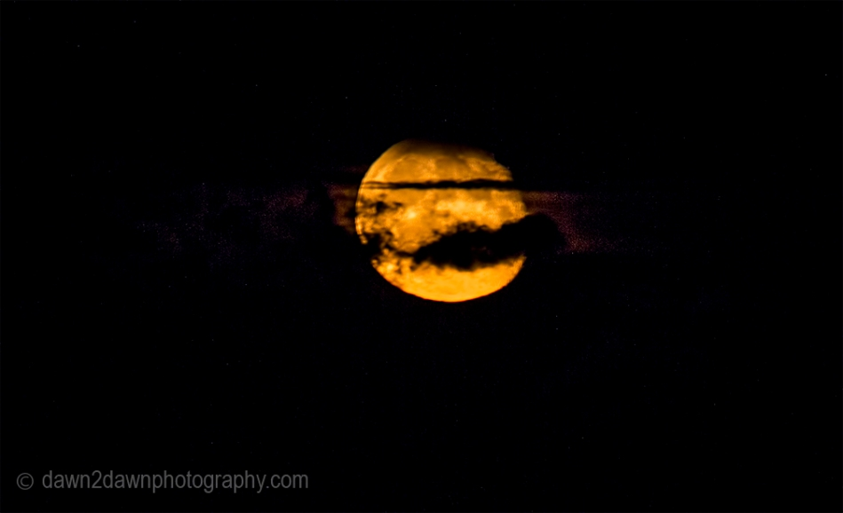 A full moon rises amongst soem passing clouds in Northern Arizona
