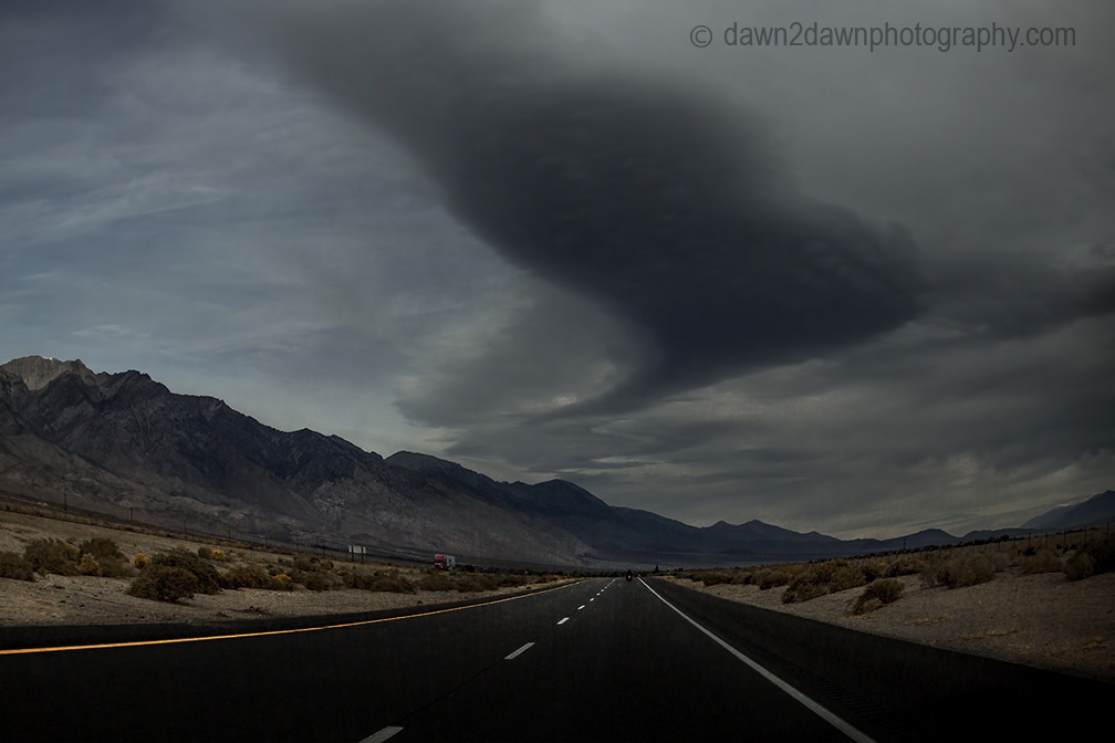 Storm clouds hover over Highway 395 in the Owens Valley, California