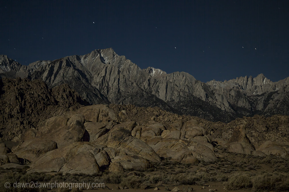 The light from a full moon shines on The Sierra Nevada Mountains near Lone Pine, California