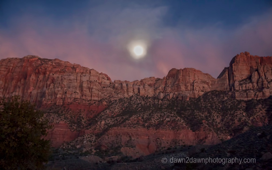 A full moon rises through the clouds and over the rim of Zion Canyon at Zion National Park,Utah