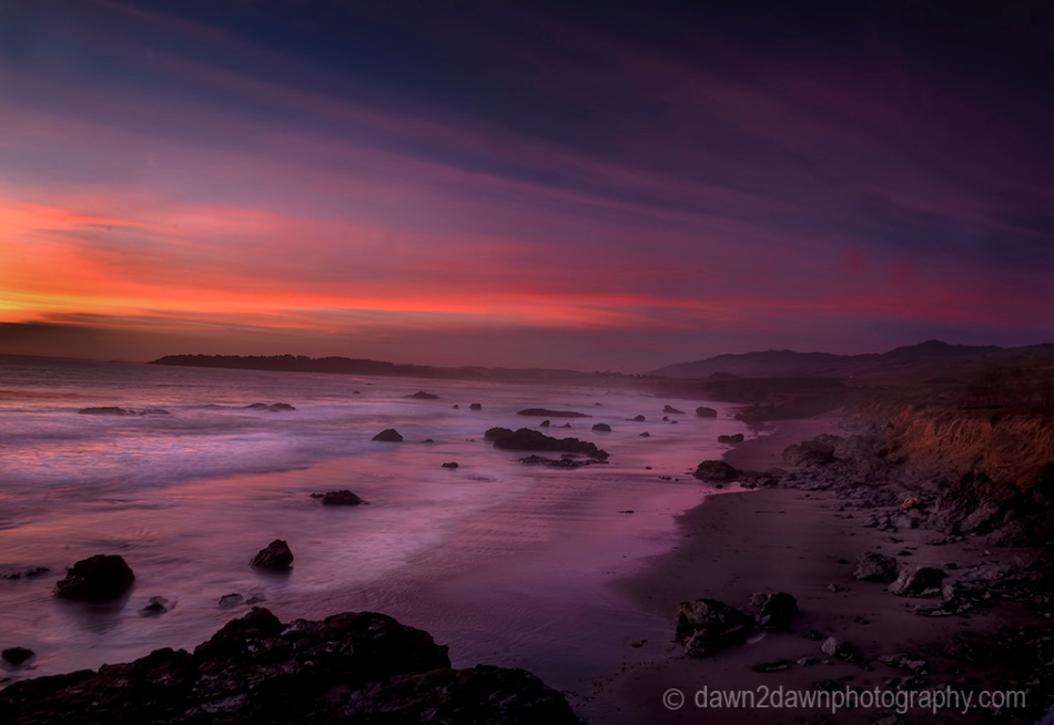The sun sets over the Pacific Ocean near San Simeon, California