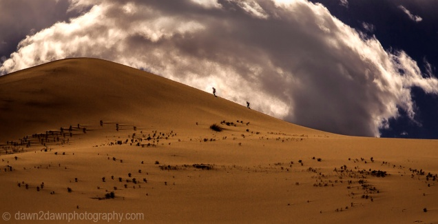 Storm clouds pass over two hikers on Eureka Dunes at Death Valley National Park, California