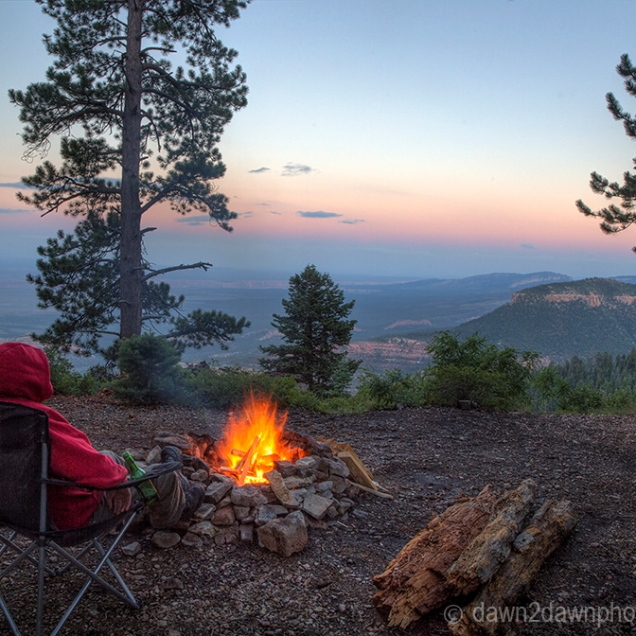 A campfire brings warmth to a camper overlooking Grand Canyon National Park from Kaibab National Forest, Arizona