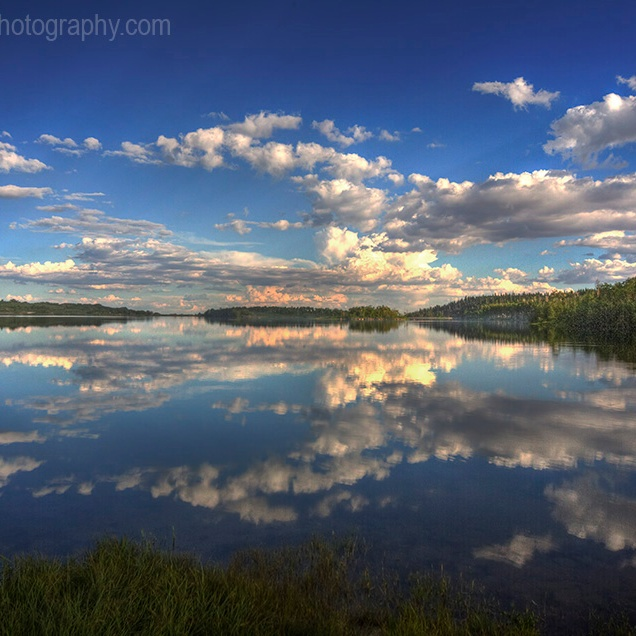 Passing clouds are reflected in the still waters of Kolob Reservoir near Zion National Park, Utah