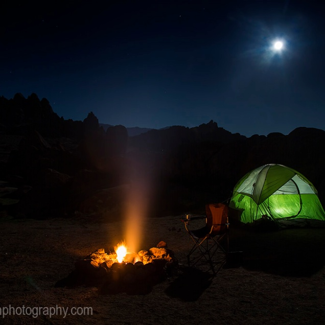 The moon rises over a campfire at Alabama Hills in the Owens Valley of California