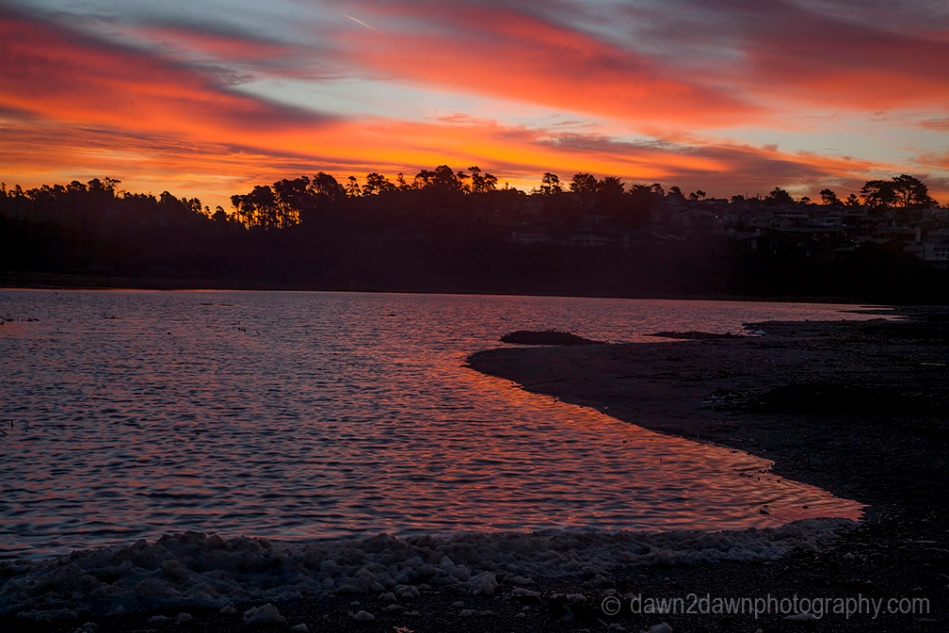 The sun rises over a lagoon at the Pacific Ocean at Cambria, California