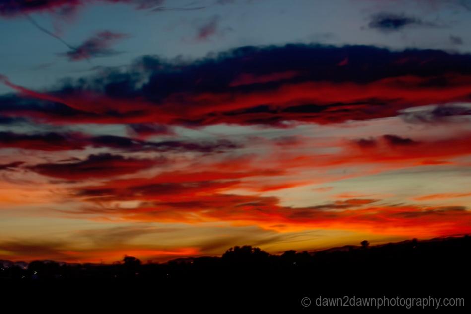 The sun sets over farmland in rural California