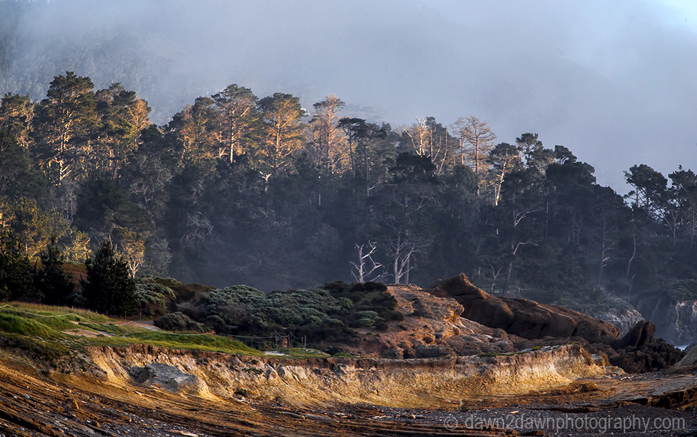 The sun sets on the rocky landscape at Point Lobos State Natural Reserve in Carmel, California