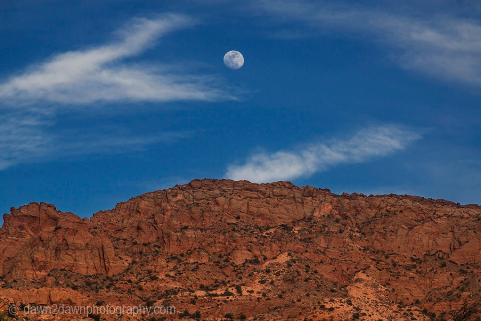 A near full moon rises over the sandstone cliffs at Vermillion Cliffs National Monument, Arizona