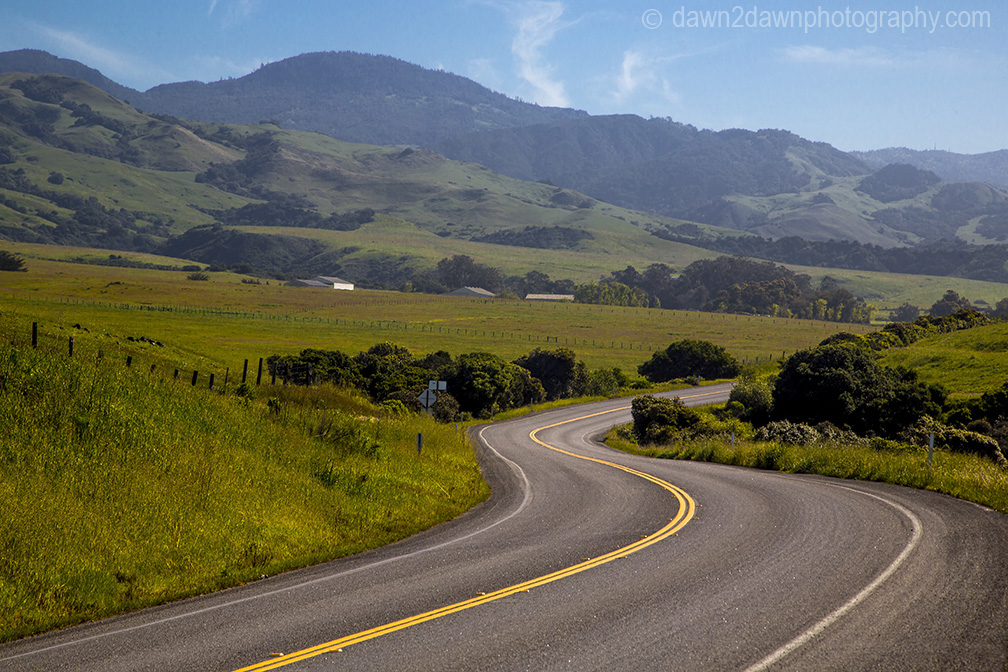 The Pacific Coast Highway winds its way through farmland along California's Pacific Ocean Coastline near San Simeon.