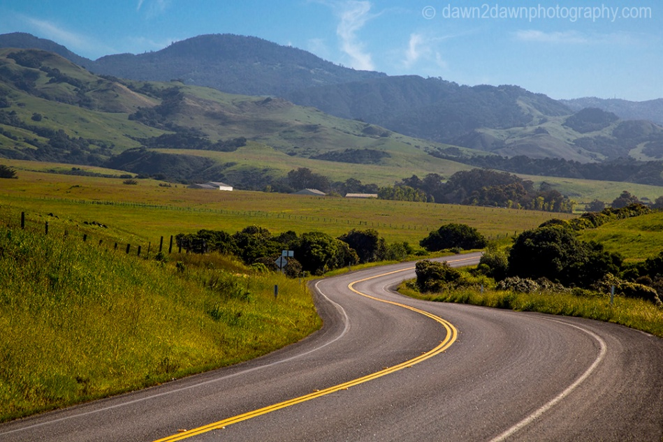 The Pacific Coast Highway winds its way through farmland along California's Pacific Ocean Coastline near San Simeon.