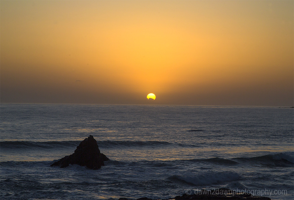 The sun sets on California's Pacific Ocean at San Simeon.