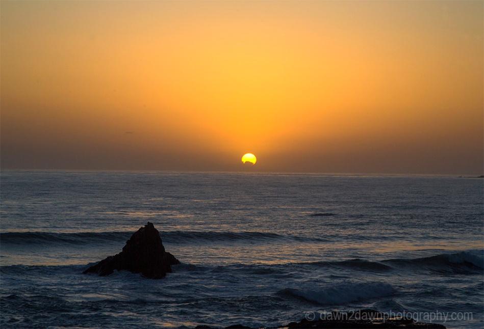 The sun sets on California's Pacific Ocean at San Simeon.