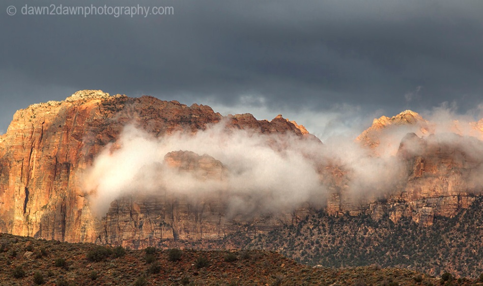 A passing storm produces clouds around The Watchman at Zion National Park, Utah