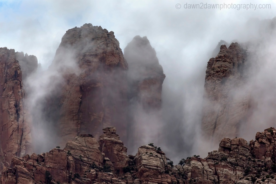 A passing thunderstorm deposits clouds around West Temple at Zion National Park, Utah