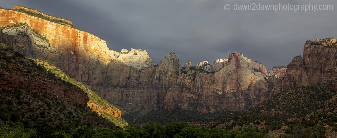 The light from the rising sun shines upon The Towers Of The Virgin at Zion National Park, Utah