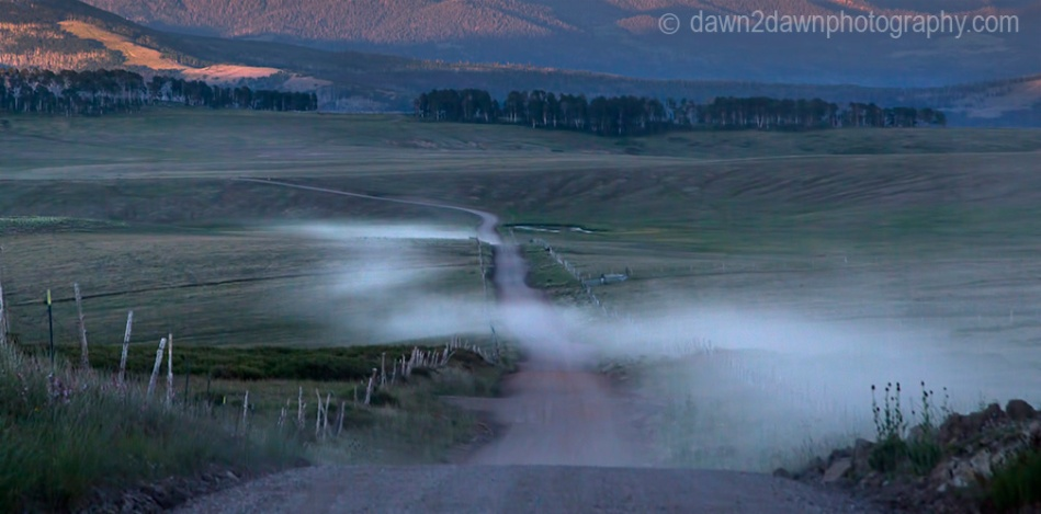 A passing vehicle has produced clouds of dust during a hot summer on a Kolob Terrace country road in Southern Utah.