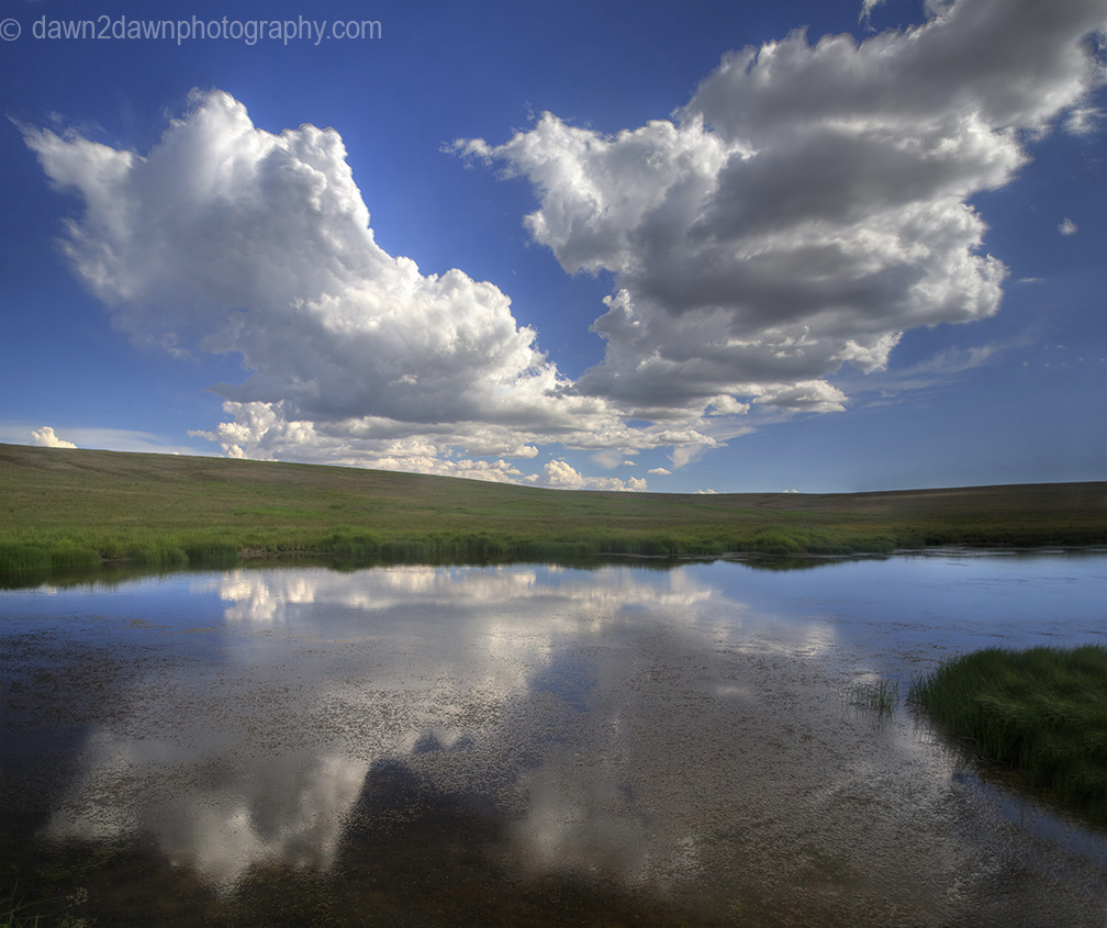 Large clouds are reflected in a small pond at Kolob Terrace in the highlands of Southern Utha