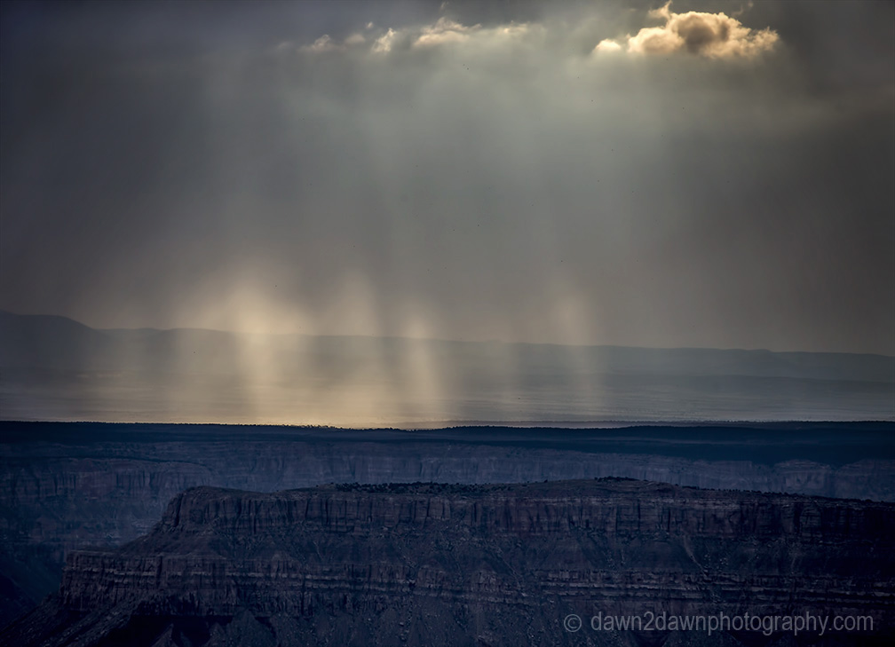 Storm clouds pass over the Grand Canyon and produce sunbeams near Timp Point, Kaibab National Forest, Arizona
