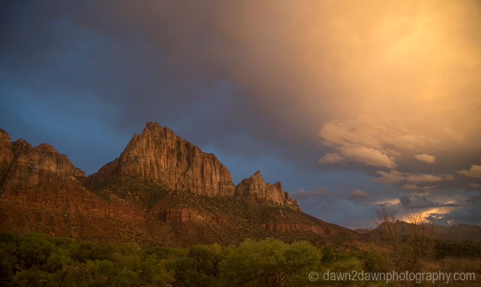 The light from the setting sun shines on the The Watchman at Zion National Park, Utah