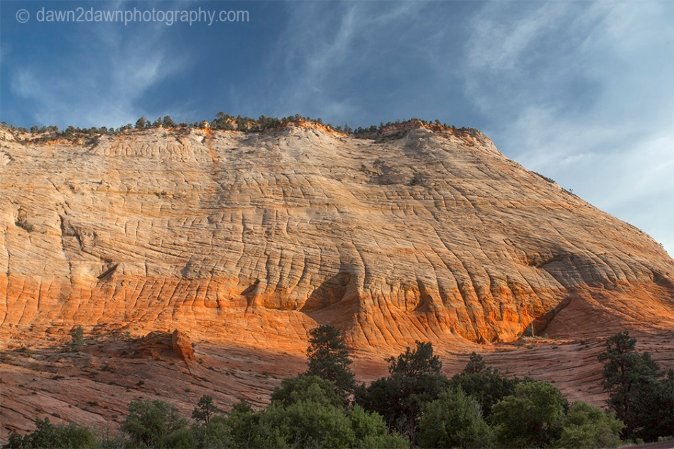 "The light from the setting sun shines upon ""Crazy Quilty Mesa"" at Zion National Park, Utah"