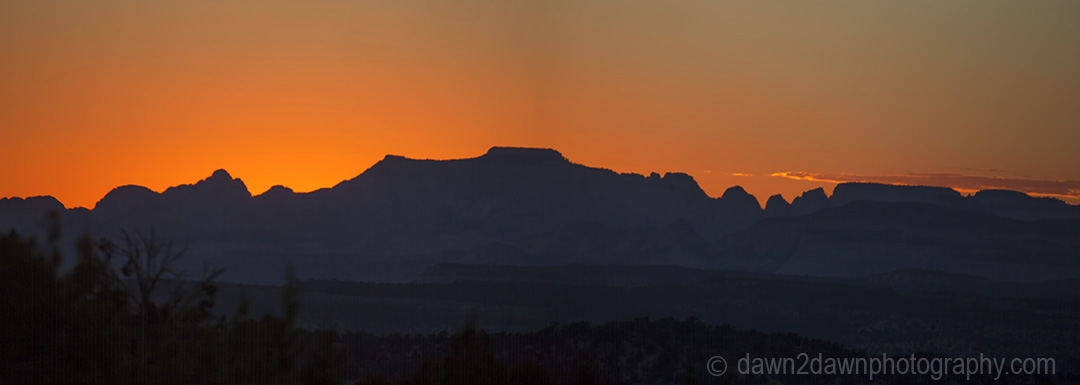 The sun sets behind the skyline of Zion National park, Utah