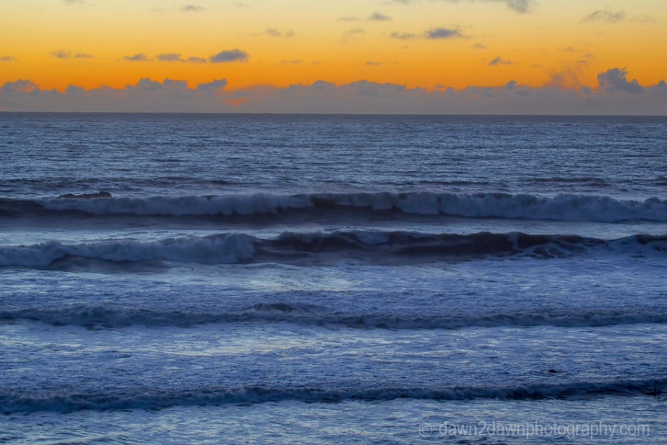 The light from the setting sun casts a soft light on clouds over the Pacific Ocean at California's central coast.