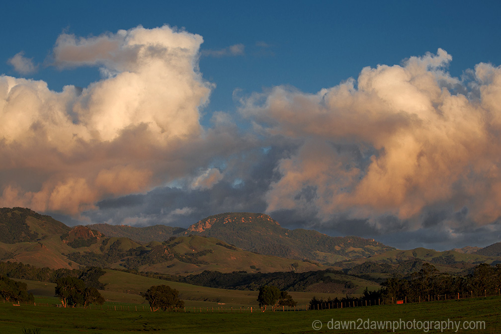 The light from the setting sun casts a soft light on clouds over the hills along California's central coast.