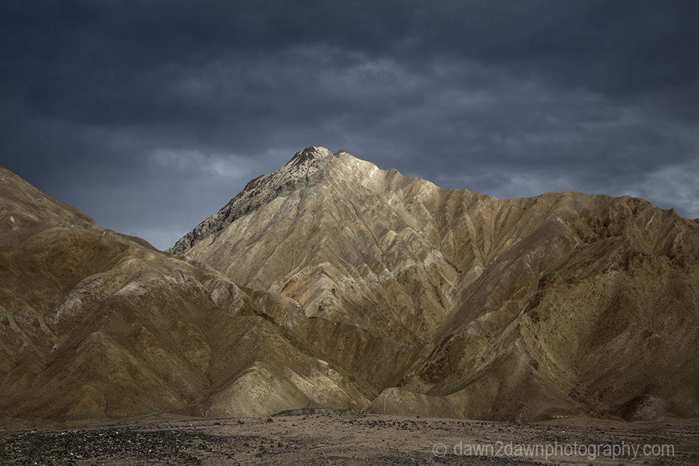 Passing storm clouds filter sunlight on the landscape at Death Valley National Park, California