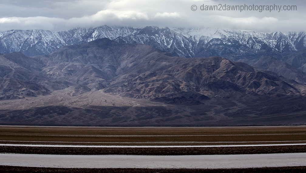 Passing storm clouds filter sunlight on the landscape at Badwater Basin at Death Valley National Park, California