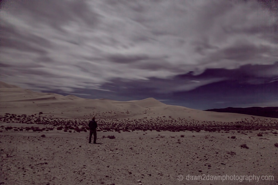 A nearly full moon rises through the clouds over Eureka Dunes at Death Valley National Park, California