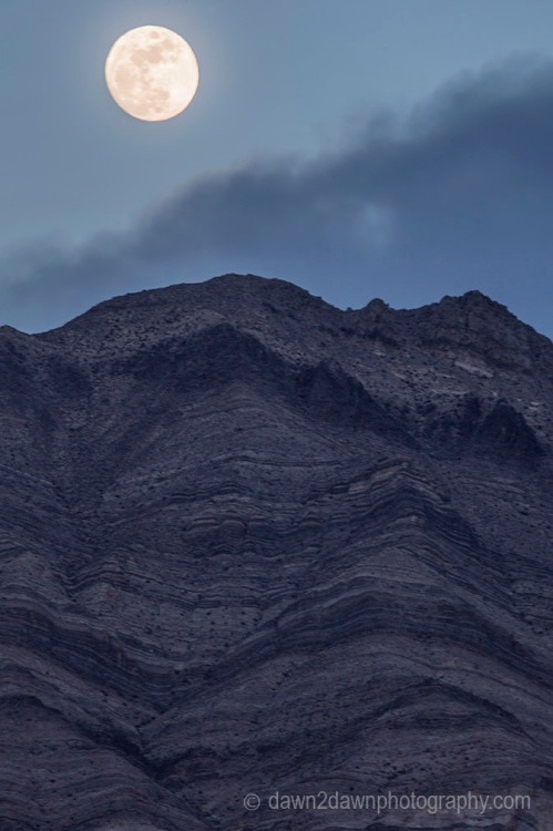 A nearly full moon rises over the Last Chance Mountains at Death Valley National Park, California