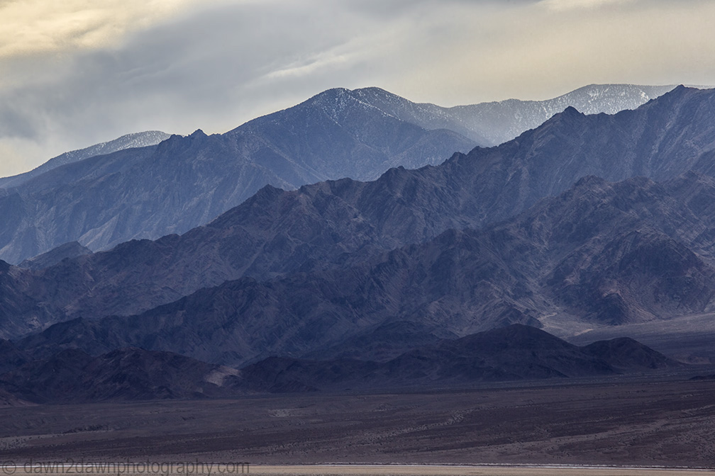 Rugged mountains line Badwater Basin At Death Valley National Park, Calfirornia