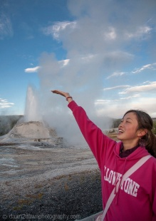 Old Faithful erupts as visitors look on at Yellwostone National Park, Wyoming.